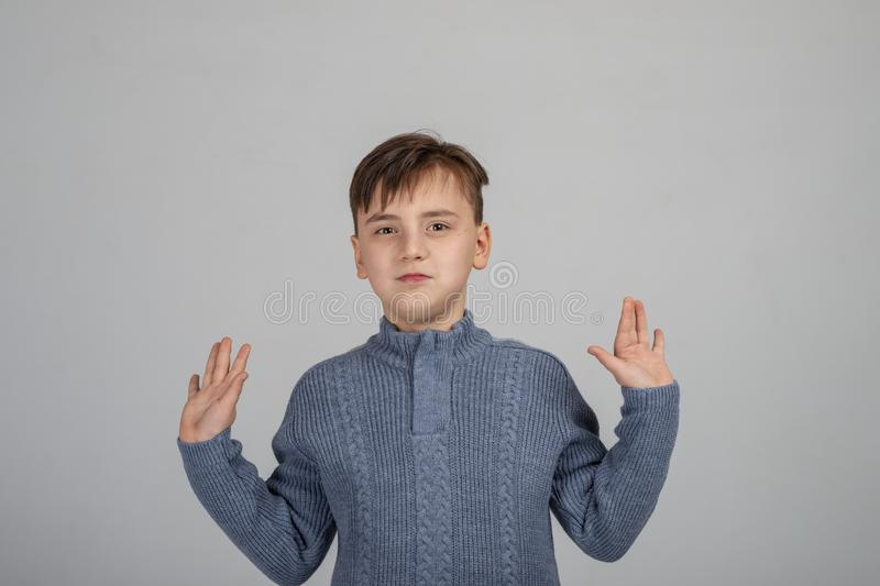 Studio shot of a serious young boy wearing a grey sweater with hands spreading aside royalty free stock images