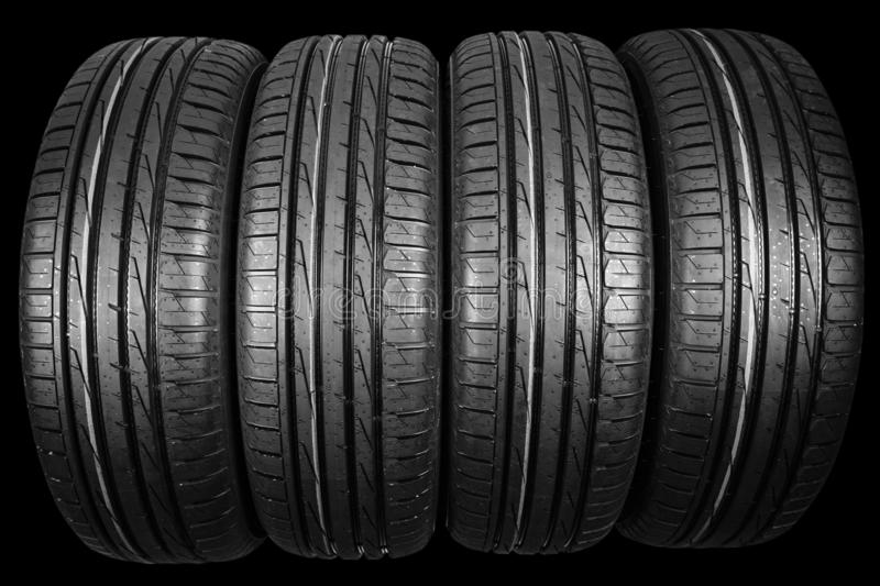 Studio shot of a set of summer car tires isolated on black background. Tire stack background. Car tyre protector close up. Black r. Ubber tire. Brand new car royalty free stock photo