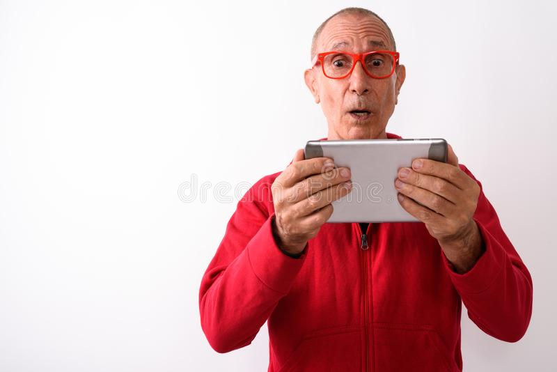Studio shot of shocked bald senior man using digital tablet whil royalty free stock photos