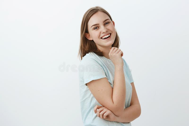 Studio shot of skillful creative and ambitious european woman in trendy t-shirt standing in profile over white wall. Turning at camera with satisfied happy and royalty free stock image