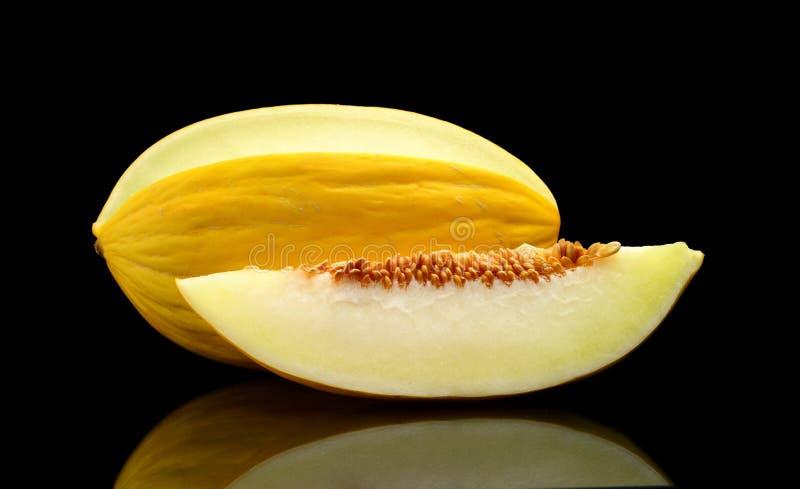 Studio shot of sliced Canary melon isolated black. Studio shot of whole and sliced yellow canary melon isolated on black background royalty free stock image