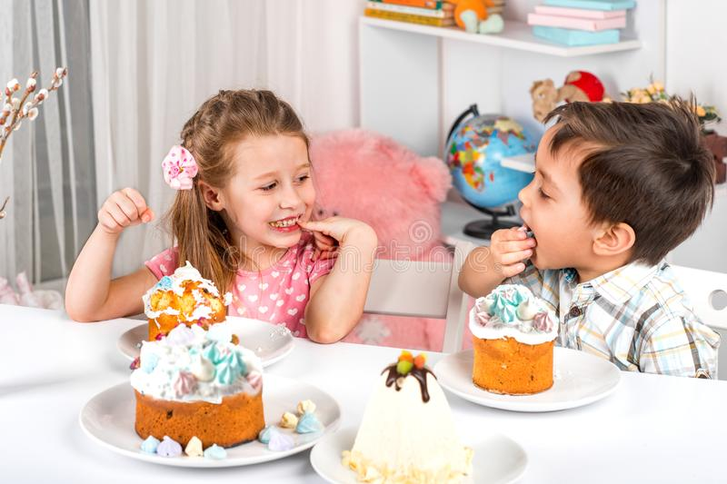 Studio shot of small children, girl and boy, sitting at a table with Easter cakes. They eat Easter with festive mood royalty free stock photos
