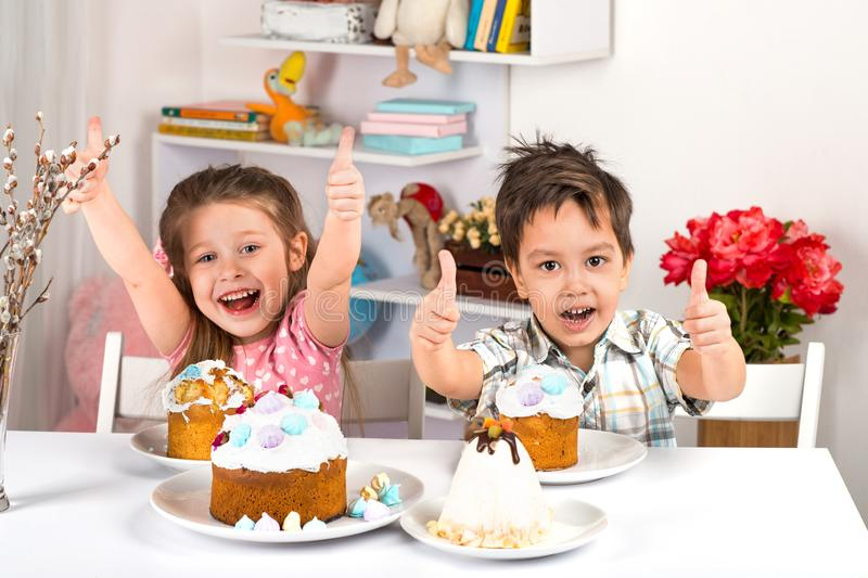 Studio shot of littlel children, girl and boy, sitting at a table with Easter cakes. They have a festive mood. Studio shot of small children, girl and boy royalty free stock image