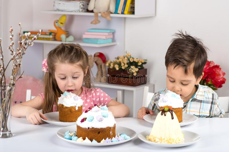 Studio shot of little children, girl and boy, sitting at a table and eating Easter cakes. They have a festive mood. Studio shot of small children, girl and boy royalty free stock images