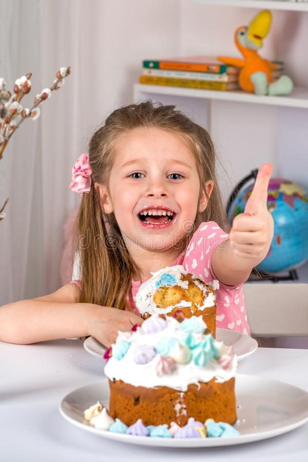 Studio shot of small girl sitting at a table and eating Easter . She have a festive mood and gestures a sign of approval stock image
