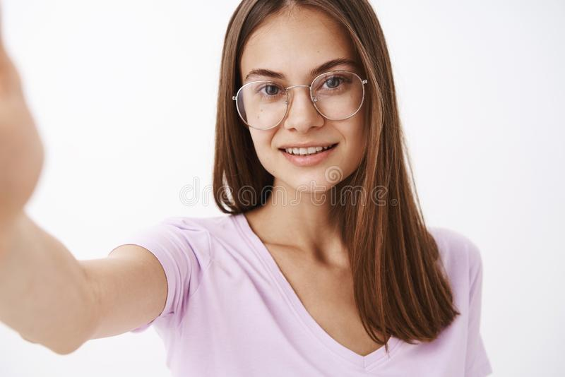 Studio shot of smart attractive and confident adult female entrepreneur in fancy glasses pulling hand forward and stock images