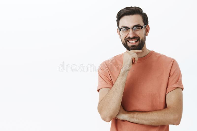 Studio shot of smart and creative happy handsome male entrepreneur in cute sight glasses rubbing beard and laughing. Joyfully listening amusing story while stock images