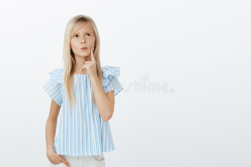 Studio shot of smart young girl with blond hair, looking up and holding finger on lip, frowning while thinking, making royalty free stock photos