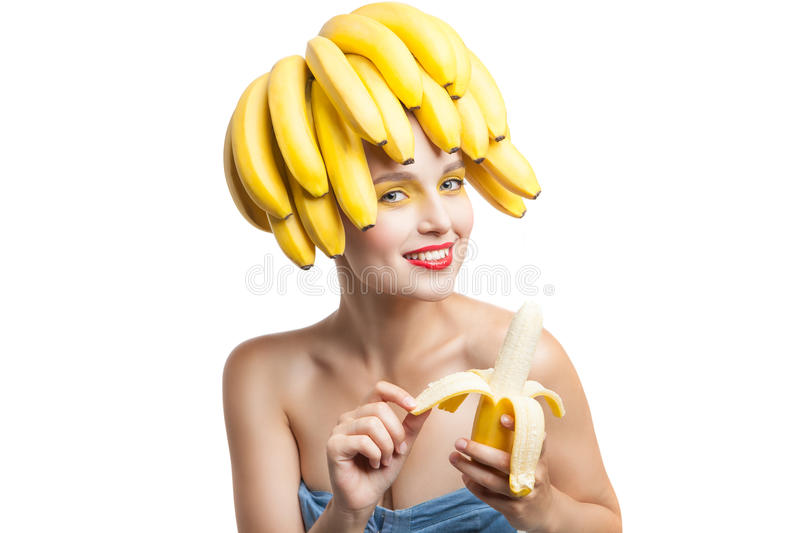 Studio shot of smiling woman peeling banana royalty free stock image