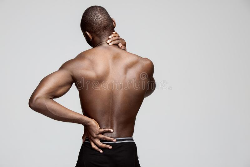 Studio shot of man with pain in neck stock images