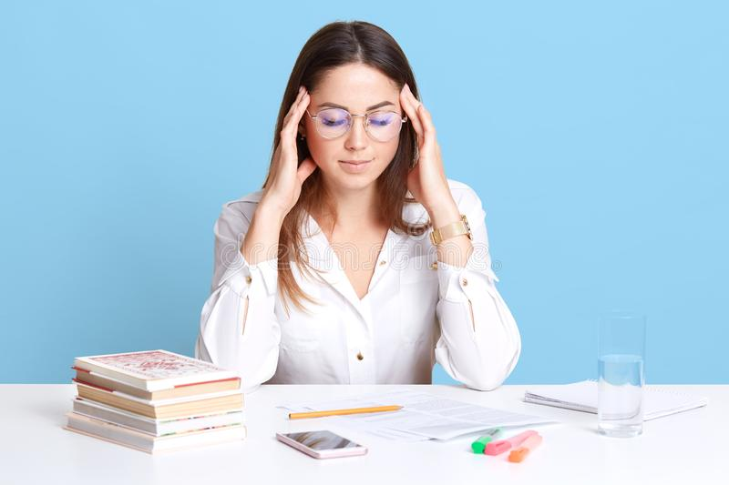 Studio shot of stressed attractive office worker sitting at table isolated over blue background in studio, touching her temples royalty free stock photography