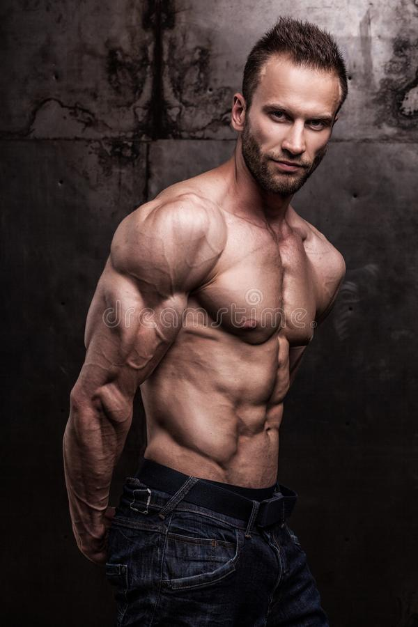 Strong athletic man on dark grunge background stock photography
