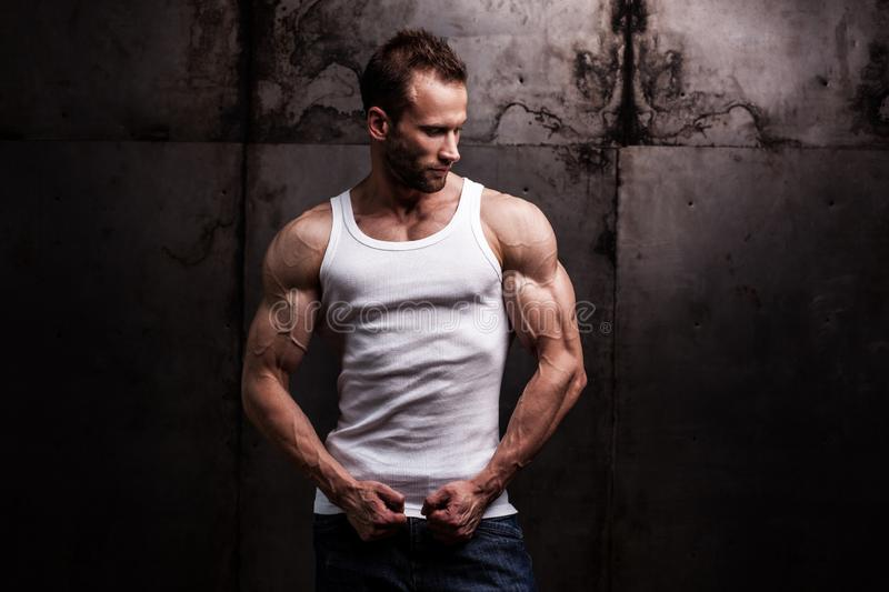 Strong athletic man on dark grunge background. Studio shot of strong athletic man wearing white shirt on dark grunge background royalty free stock images