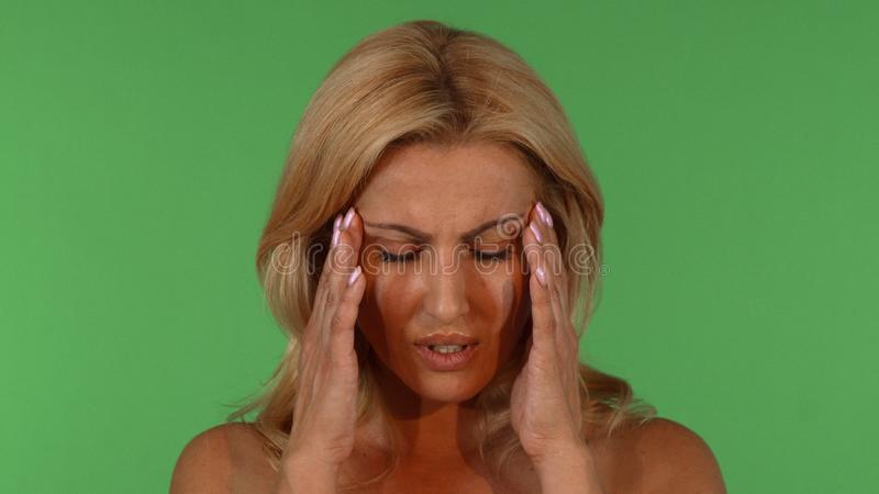 Beautiful mature woman having headache royalty free stock photo