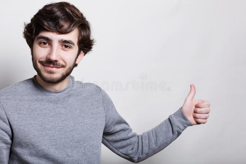 A studio shot of stylish man with thick eyebrows big dark eyes trendy hairstyle and beard dressed in gray sweater stranding over w royalty free stock photo