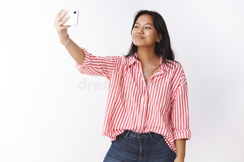 Studio shot of stylish young cute asian woman taking selfie to impress followers in internet with new trendy blouse royalty free stock photo