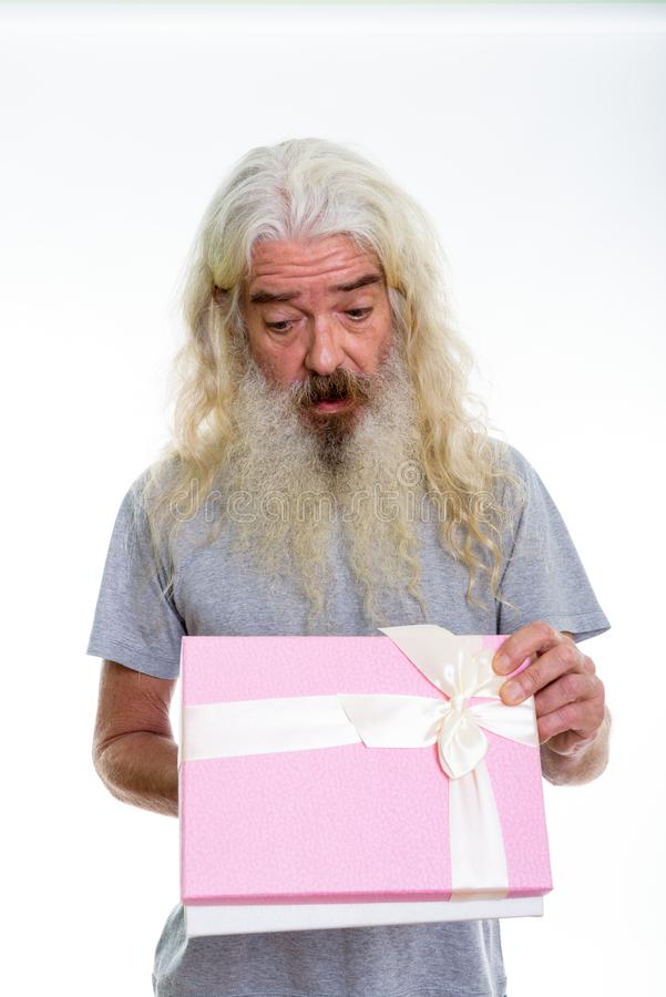 Studio shot of surprised senior bearded man opening gift box rea. Dy for Valentine`s day stock photography