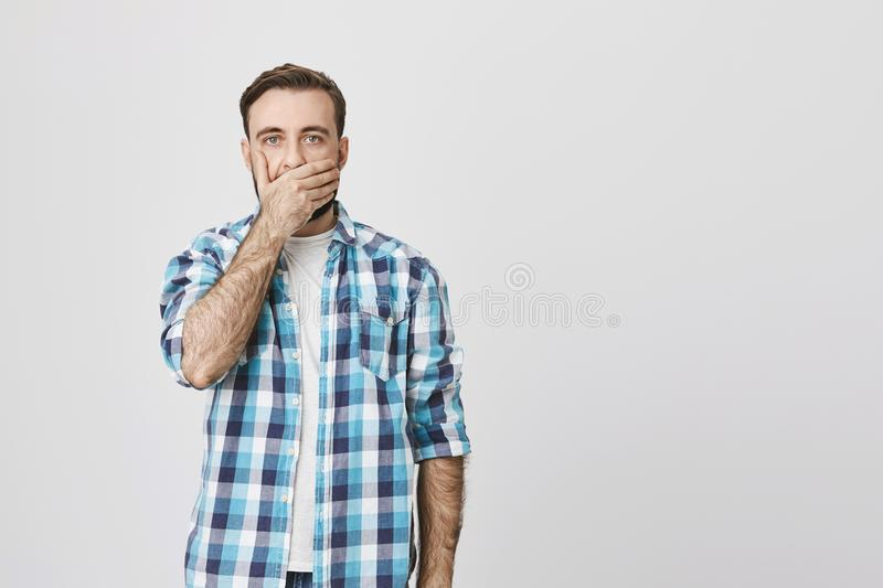 Studio shot of terrifired adult man in checked shirt, covering mouth with hand and who is about to cry, against gray. Wall. Person just saw terrible accident royalty free stock photos