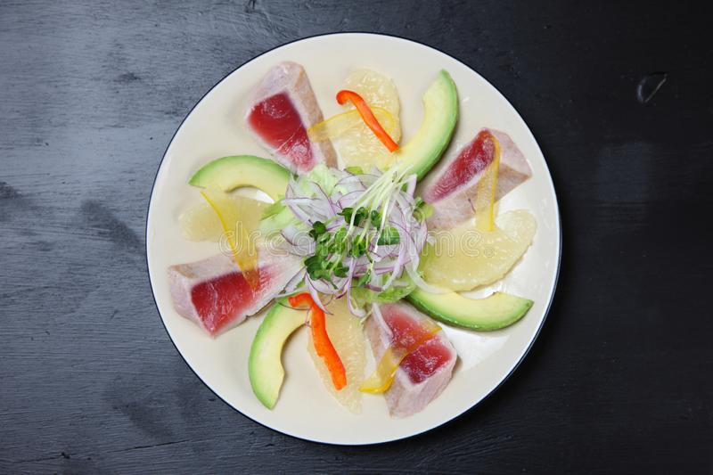 Tuna and avocado carpaccio on a dining table royalty free stock images