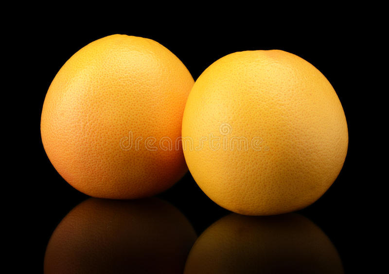 Studio shot of two grapefruits isolated on black background. Two grapefruits isolated on black background royalty free stock images