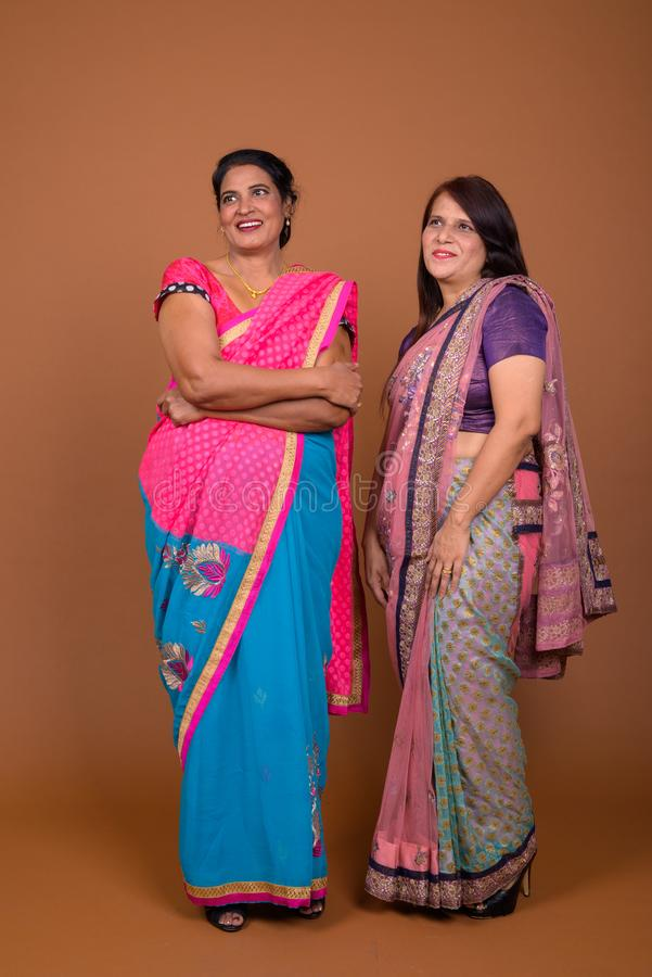 Two mature Indian women wearing Sari Indian traditional clothes. Studio shot of two mature Indian women wearing Sari Indian traditional clothes together against stock image