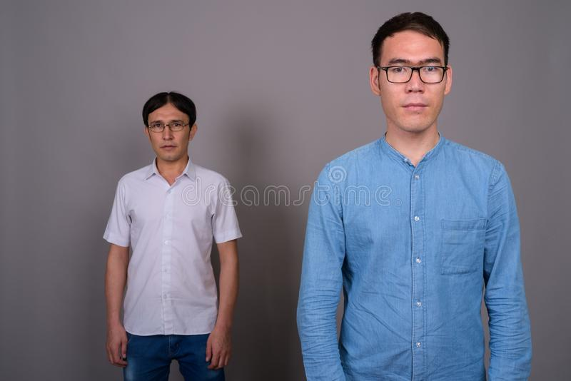 Two young Asian businessmen wearing eyeglasses together against royalty free stock image