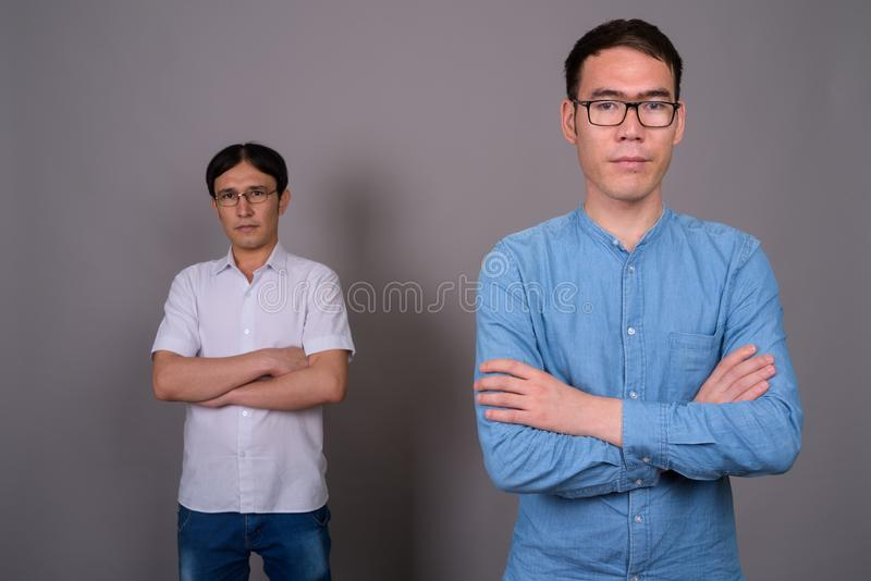 Two young Asian businessmen wearing eyeglasses together against royalty free stock photography