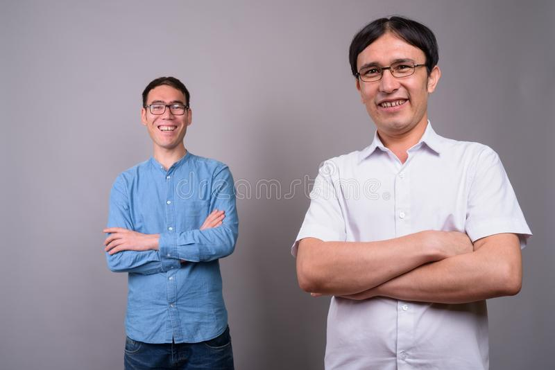 Two young Asian businessmen wearing eyeglasses together against stock image