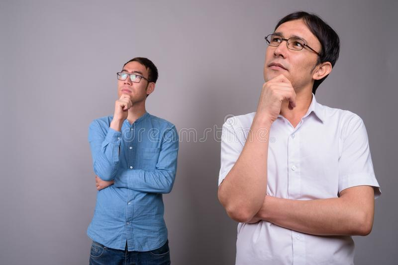 Two young Asian businessmen wearing eyeglasses together against stock photos