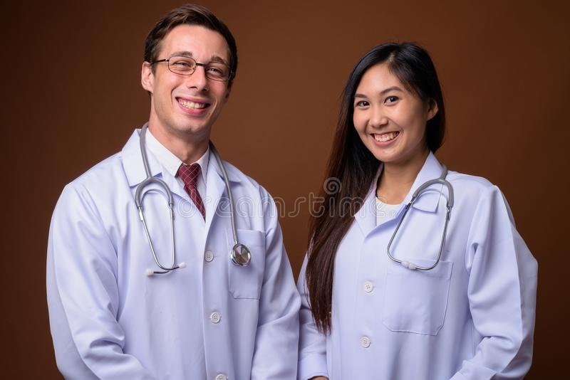 Studio shot of two young doctors together against brown backgrou royalty free stock images