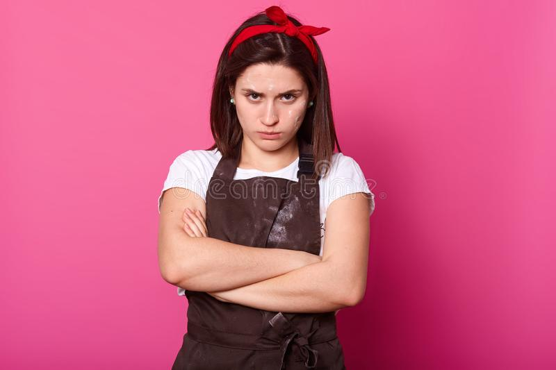 Studio shot of upset Caucasian housewife standing with arms folded, looks offended, wearing t shirt, apron and hair band, isolated royalty free stock photos