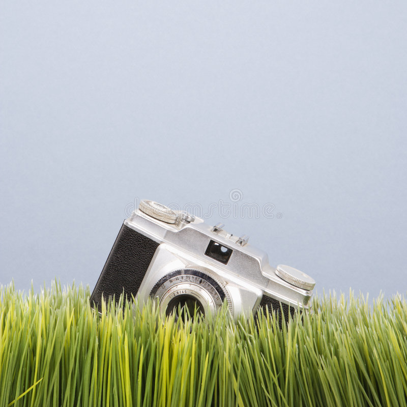 Studio shot of vintage camera in grass. stock images