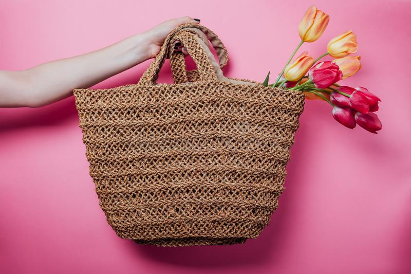 Studio shot of woman holding a straw bag with tulips on pink background. Spring sale in stores. Accessories royalty free stock photo
