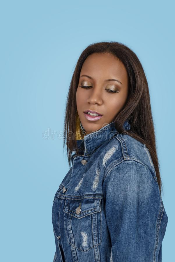 Studio shot of the young woman of the mulatta with make up wearing jeans dress against blue background royalty free stock images