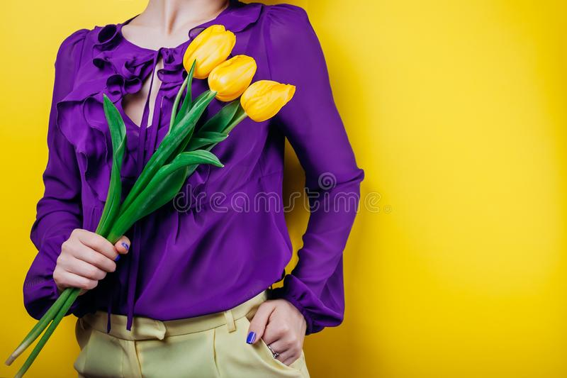 Studio shot of a woman wearing spring outfit and holding yellow tulips stock photos