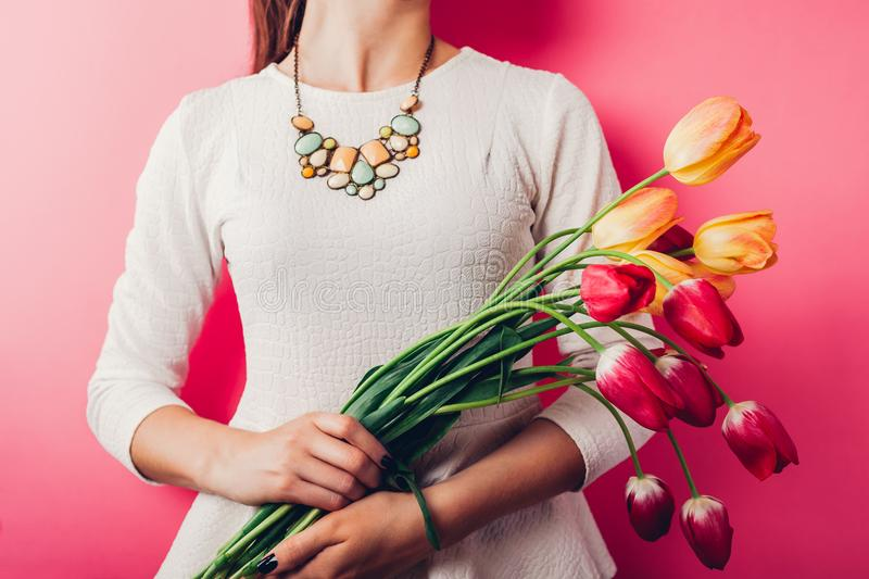 Studio shot of woman wearing spring outfit and holding tulips on pink background. Beauty and fashion concept royalty free stock images