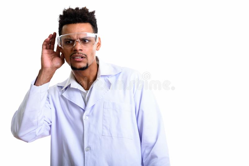 Studio shot of young African man doctor listening. Isolated against white background stock photography