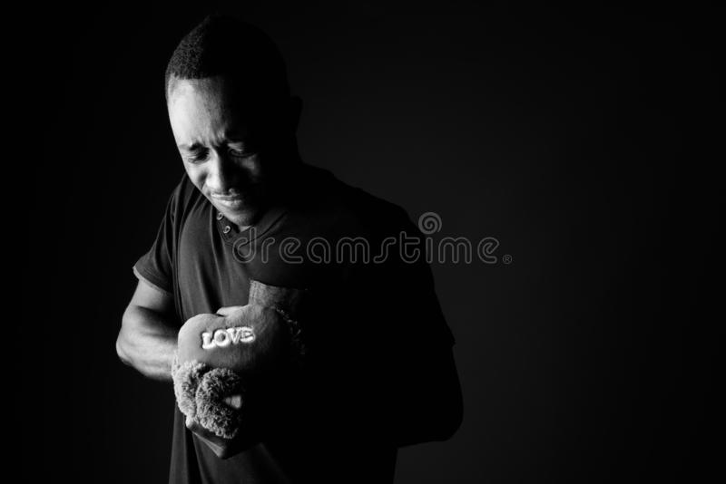 Sad Young African Man With Teddy Bear And Love Sign Text In Black
