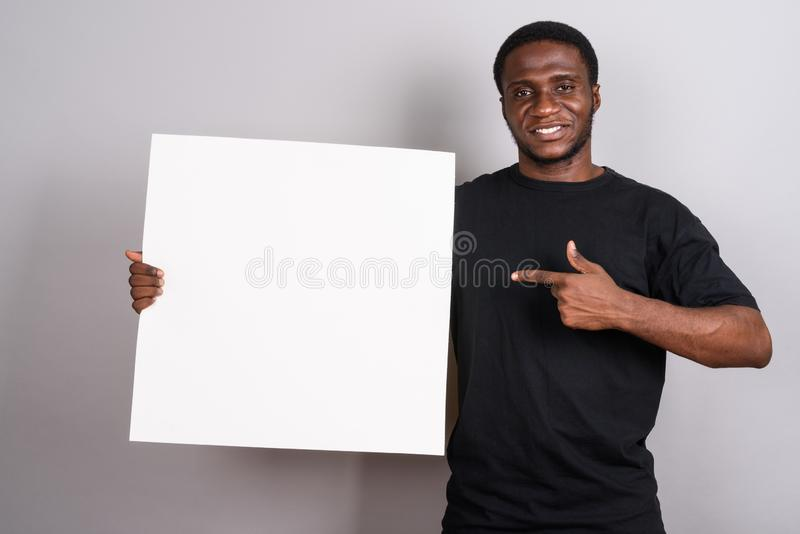 Young African man wearing black shirt against gray background royalty free stock photo