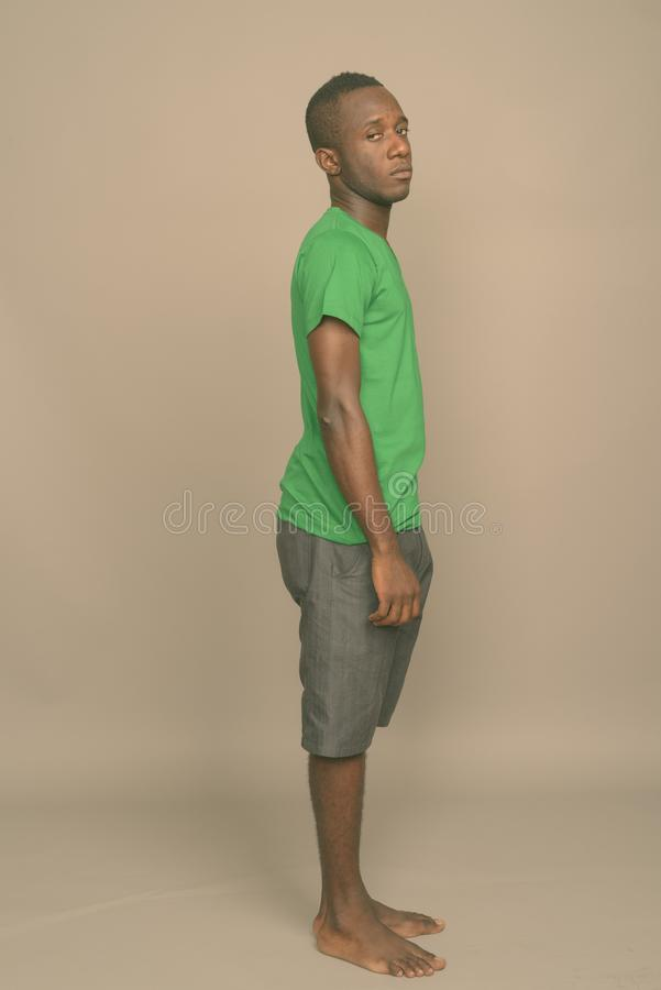 Young African man wearing green shirt against gray background stock images