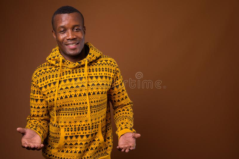 Studio shot of young African man against brown background. Studio shot of young African man wearing hoodie against brown background stock photos