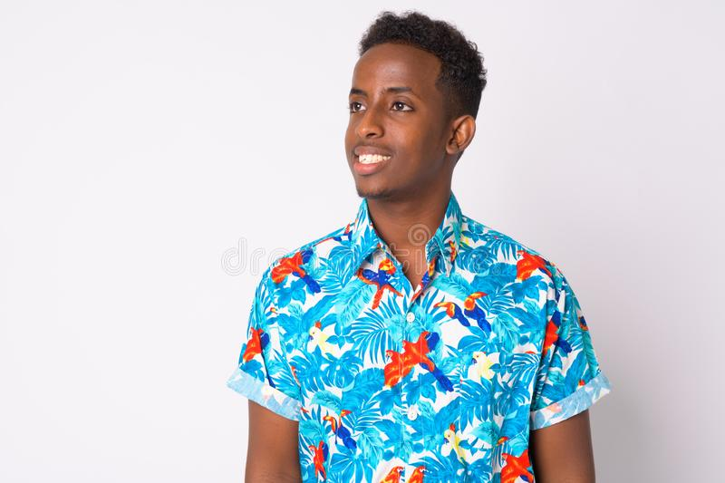Happy young African tourist man with Afro hair thinking. Studio shot of young African tourist man with Afro hair against white background royalty free stock images