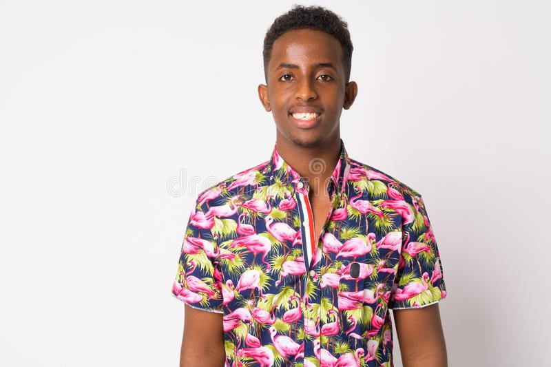 Portrait of happy young African tourist man with Afro hair smiling. Studio shot of young African tourist man with Afro hair against white background royalty free stock images