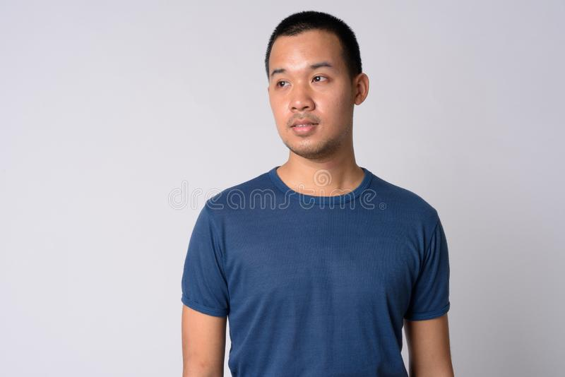 Portrait of young Asian man with short hair thinking stock photo