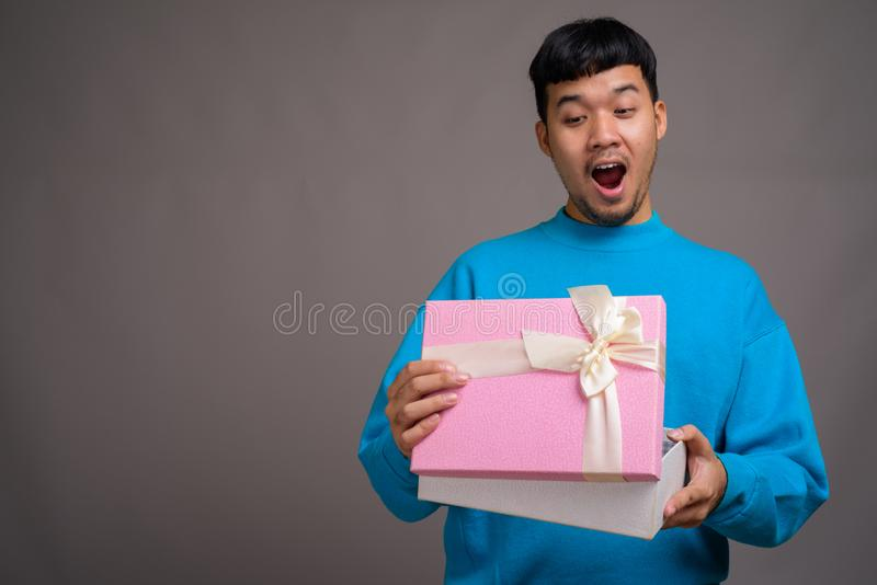 Portrait of young Asian man holding gift box. Studio shot of young Asian man wearing blue sweater while holding gift box against gray background royalty free stock photography
