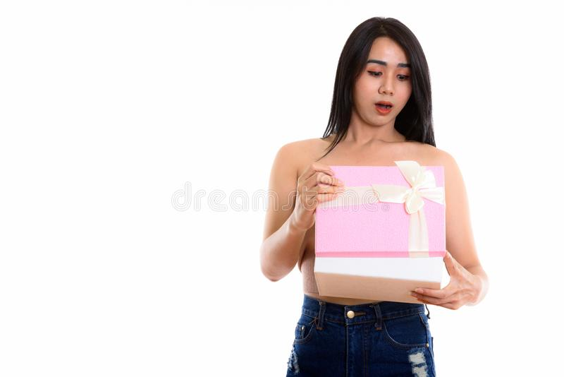 Studio shot of young Asian transgender woman opening gift box wh. Ile looking shocked royalty free stock images