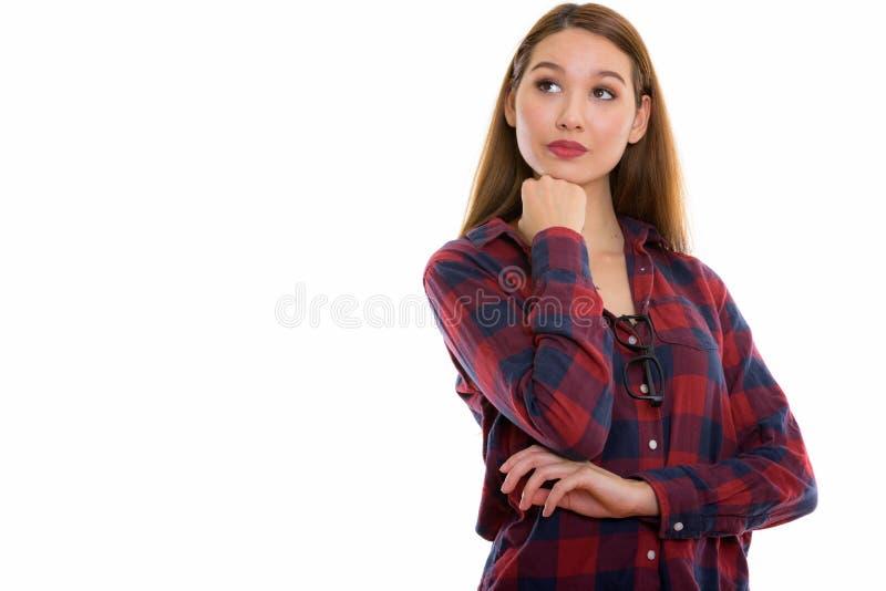 Studio shot of young beautiful Asian woman thinking while lookin stock image