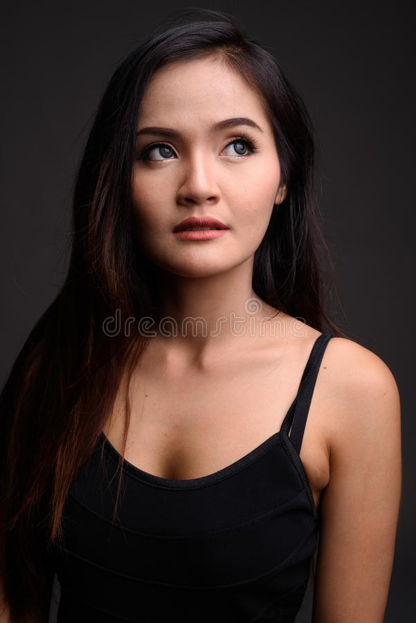 Young beautiful Asian woman thinking against gray background royalty free stock images