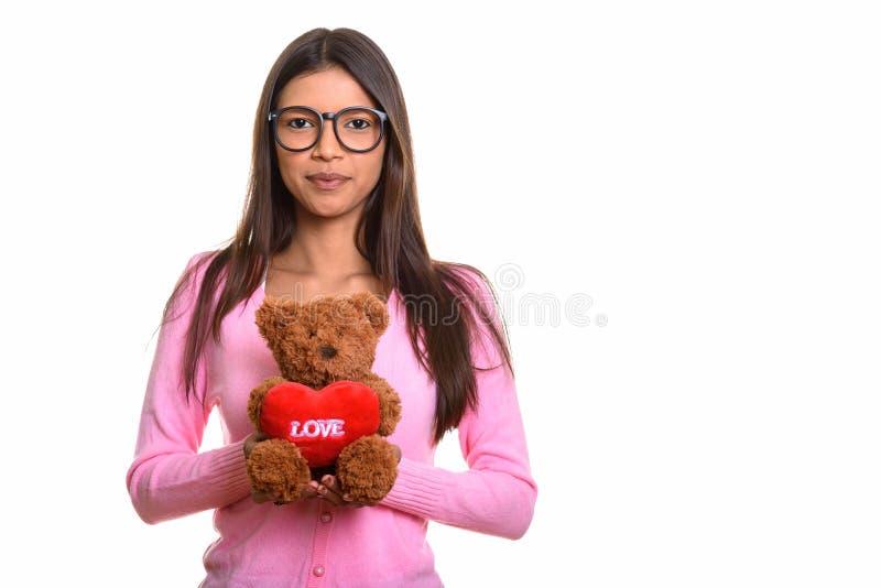 Studio shot of young beautiful Brazilian nerd woman holding tedd royalty free stock image