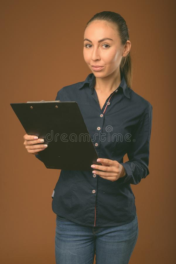 Studio shot of young beautiful businesswoman against brown background stock images